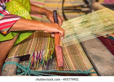Closeup old woman hands weaving mats from dry reed.
