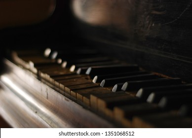 Closeup of an old wooden piano keybord in a vintage atmosphere. Interior detail symbolizing music