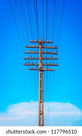 Closeup of old wooden telegraph pole, blue sky