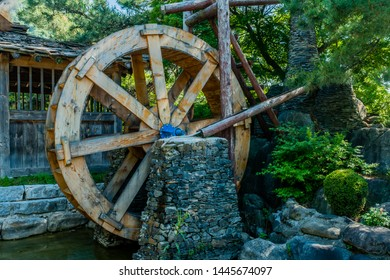 Closeup of old wooden water wheel and mill house at public park in South Korea.