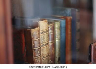 Closeup of old, worn books in a glass case