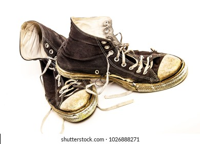 Closeup of old worn out, ripped pair of black and white retro high top tennis shoes isolated on white background