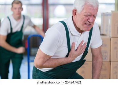 Close-up of older warehouse worker having a heart attack