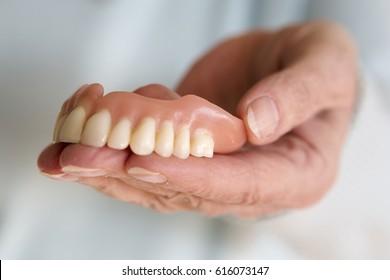closeup of older womans hand holding a teeth denture