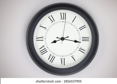 Close-up of a  old-fashioned antiquated wall clock with roman numerals on the clock face. Clock with black frame on a white background. Antique pointers showing the time.  front view of the watch