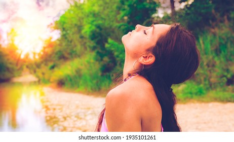 close-up on an athletic young woman performing yoga-asanas by the river. Fitness, sport, people and healthy lifestyle concept.