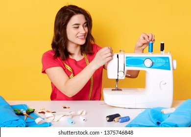 Closeup on attractive seamstress putting needle into sewing machine, has happy facial expression, wearing red casual t shirt, surrounded different sewing equipment. Creating and design concept.