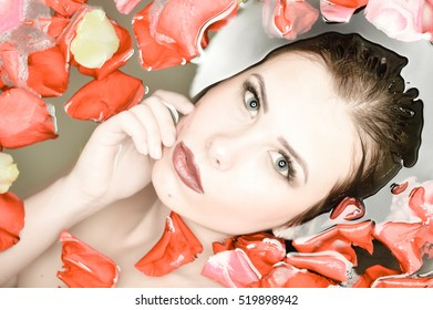 Closeup on attractive sensual woman relaxing in spa bath with milk and flower rose petals background