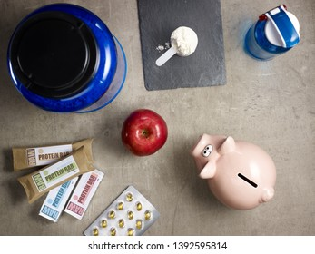 Closeup on big blue protein jar, shaker, measuring spoon with powder, raw protein bars, red apple, sport supplements in tablets and piggy bank laying on the floor.