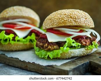 Close-up on big tasty hamburgers on wooden table