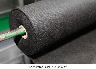A close-up on black biodegradable polypropylene saturated bonded spunbond, spunlaid non woven fabric roll.