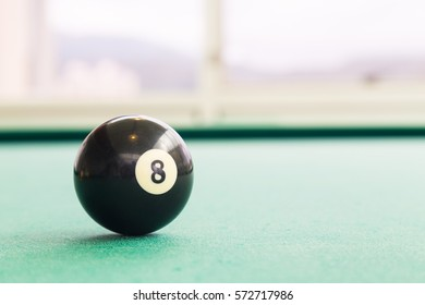 Closeup on black snooker pool billards ball on table with green surface