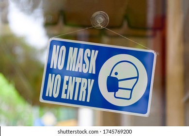 "Close-up on a blue closed sign in the window of a shop displaying the message ""No mask, no entry""."