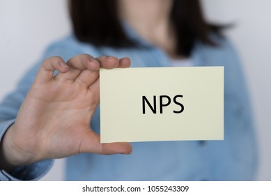 Closeup on business woman holding a card with NPS NET PROMOTER SCORE message, business concept image with soft focus background