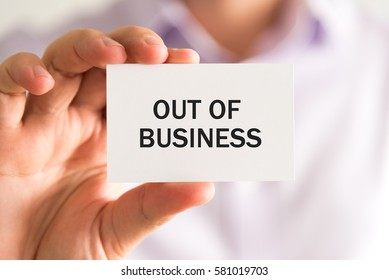 Closeup on businessman holding a card with text OUT OF BUSINESS, business concept image with soft focus background
