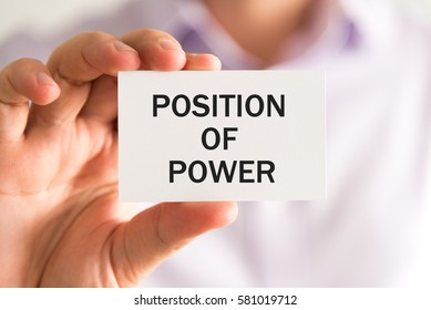 Closeup on businessman holding a card with text POSITION OF POWER, business concept image with soft focus background