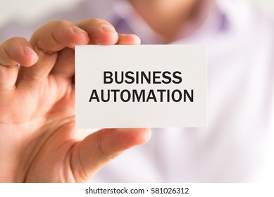 Closeup on businessman holding a card with text BUSINESS AUTOMATION, business concept image with soft focus background