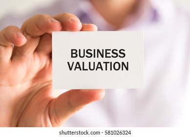 Closeup on businessman holding a card with text BUSINESS VALUATION, business concept image with soft focus background