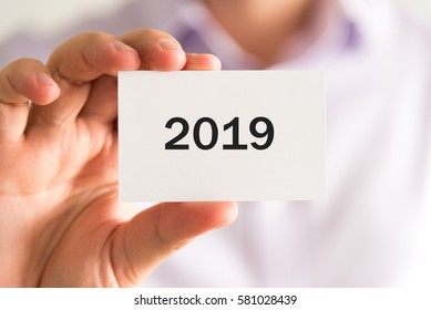 Closeup on businessman holding a card with text year 2019, business concept image with soft focus background
