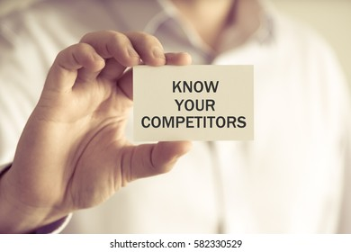 Closeup on businessman holding a card with text KNOW YOUR COMPETITORS, business concept image with soft focus background and vintage tone