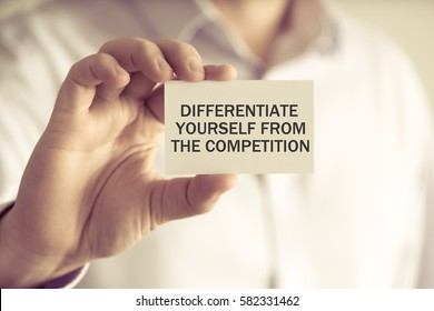 Closeup on businessman holding a card with text DIFFERENTIATE YOURSELF FROM THE COMPETITION, business concept image with soft focus background and vintage tone
