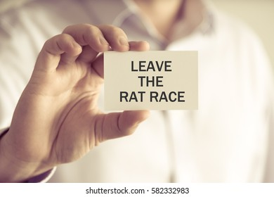 Closeup on businessman holding a card with text LEAVE THE RAT RACE, business concept image with soft focus background and vintage tone