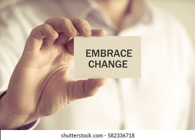 Closeup on businessman holding a card with text EMBRACE CHANGE, business concept image with soft focus background and vintage tone