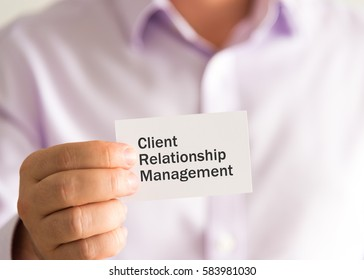 Closeup on businessman holding a card with text CRM Client Relationship Management, business concept image with soft focus background