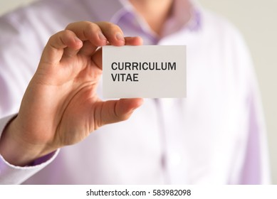 Closeup on businessman holding a card with text CV CURRICULUM VITAE, business concept image with soft focus background