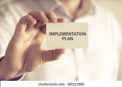 Closeup on businessman holding a card with text IMPLEMENTATION PLAN, business concept image with soft focus background and vintage tone