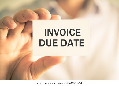 Closeup on businessman holding a card with text INVOICE DUE DATE, business concept image with soft focus background and vintage tone
