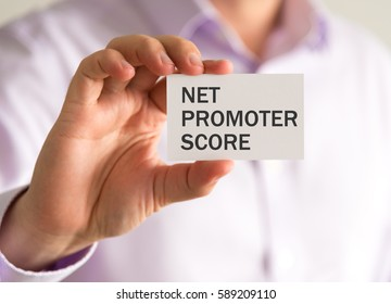 Closeup on businessman holding a card with NPS NET PROMOTER SCORE message, business concept image with soft focus background and vintage tone