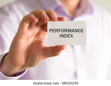 Closeup on businessman holding a card with PERFORMANCE INDEX message, business concept image with soft focus background and vintage tone