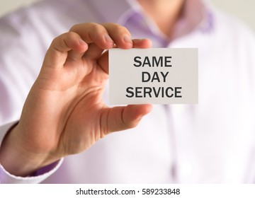 Closeup on businessman holding a card with SAME DAY SERVICE message, business concept image with soft focus background and vintage tone