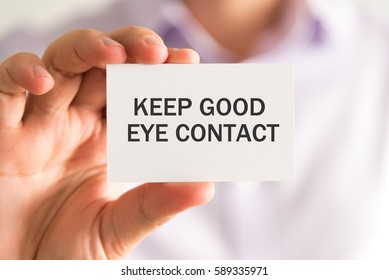 Closeup on businessman holding a card with KEEP GOOD EYE CONTACT message, business concept image with soft focus background and vintage tone