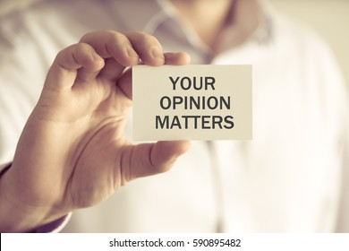 Closeup on businessman holding a card with text YOUR OPINION MATTERS, business concept image with soft focus background and vintage tone