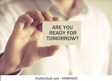 Closeup on businessman holding a card with text ARE YOU READY FOR TOMORROW ?, business concept image with soft focus background and vintage tone