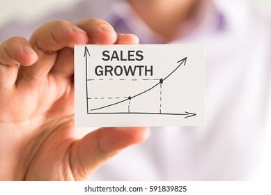 Closeup on businessman holding a card with SALES GROWTH rising arrow and chart, business concept image with soft focus background