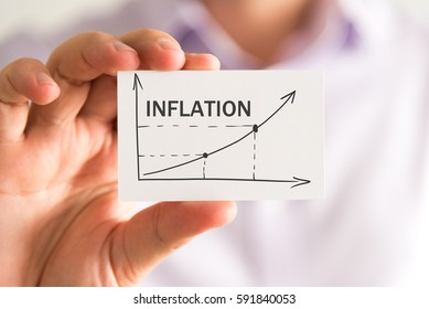 Closeup on businessman holding a card with INFLATION rising arrow and chart, business concept image with soft focus background