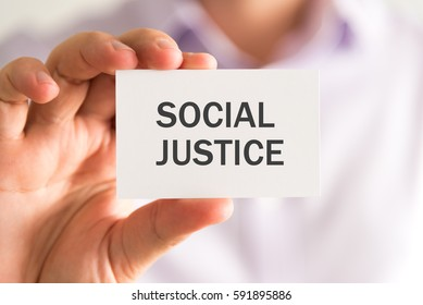 Closeup on businessman holding a card with SOCIAL JUSTICE message, business concept image with soft focus background