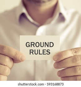 Closeup on businessman holding a card with text GROUND RULES, business concept image with soft focus background and vintage tone
