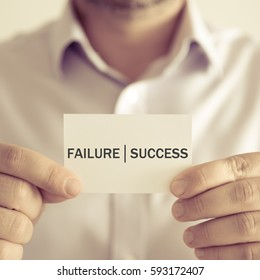 Closeup on businessman holding a card with text FAILURE SUCCESS, business concept image with soft focus background and vintage tone