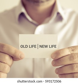 Closeup on businessman holding a card with text OLD LIFE NEW LIFE, business concept image with soft focus background and vintage tone