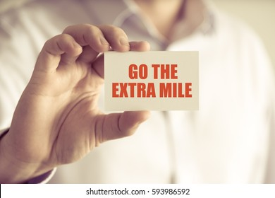 Closeup on businessman holding a card with text GO THE EXTRA MILE, business concept image with soft focus background and vintage tone
