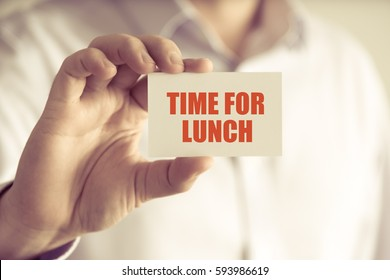 Closeup on businessman holding a card with text TIME FOR LUNCH, business concept image with soft focus background and vintage tone