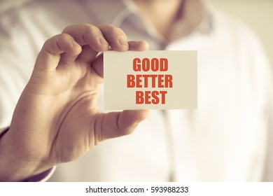 Closeup on businessman holding a card with text GOOD BETTER BEST, business concept image with soft focus background and vintage tone