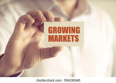 Closeup on businessman holding a card with text GROWING MARKETS, business concept image with soft focus background and vintage tone