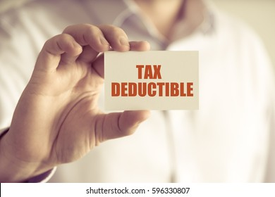 Closeup on businessman holding a card with text TAX DEDUCTIBLE, business concept image with soft focus background and vintage tone