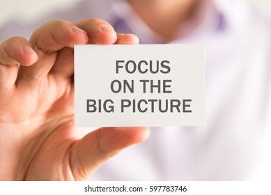 Closeup on businessman holding a card with FOCUS ON THE BIG PICTURE message, business concept image with soft focus background