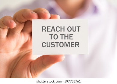 Closeup on businessman holding a card with REACH OUT TO THE CUSTOMER message, business concept image with soft focus background
